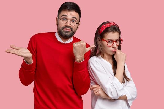 Homem intrigado aponta para mulher ofendida com expressão carrancuda