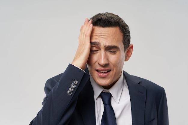 Homem intrigado de terno tocando a cabeça com problemas nas mãos no trabalho