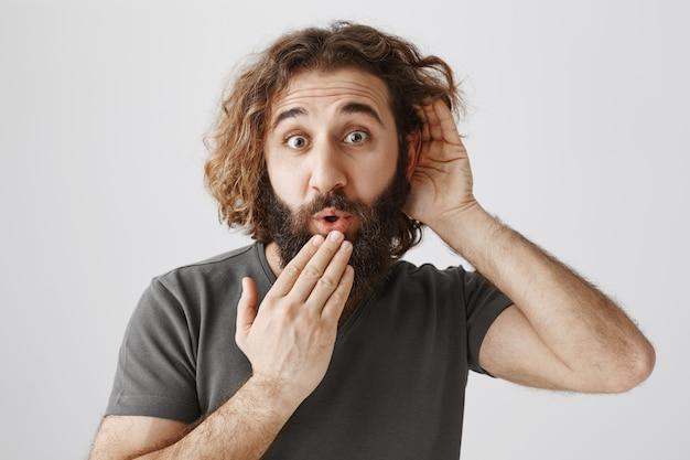 Homem intrigado do oriente médio bisbilhotando, parecendo surpreso e surpreso