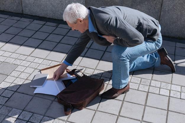 Homem intrigado e amedrontado de pé com um joelho no chão e segurando uma mão no peito enquanto verifica as coisas da bolsa