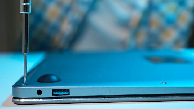 Homem irreconhecível aparafusando parafusos na tampa do laptop após o reparo