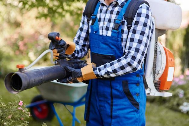 Homem irreconhecível com equipamento moderno de jardinagem