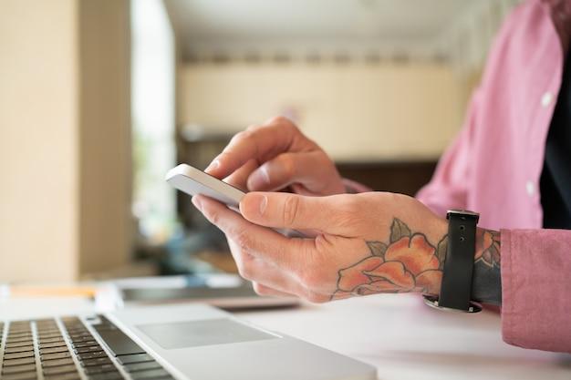 Homem irreconhecível com tatuagem rosa usando smartphone