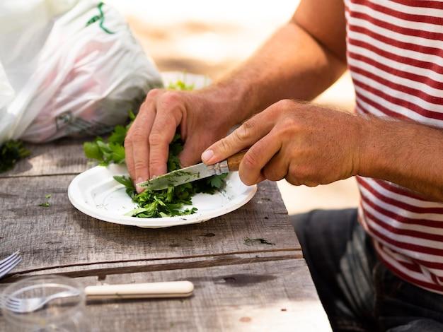 Homem irreconhecível, cortando a salsa na chapa em dia ensolarado