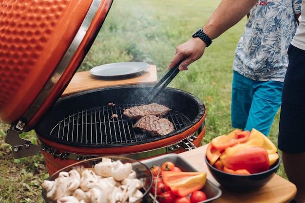 Homem irreconhecível, cozinhar carne na grelha.