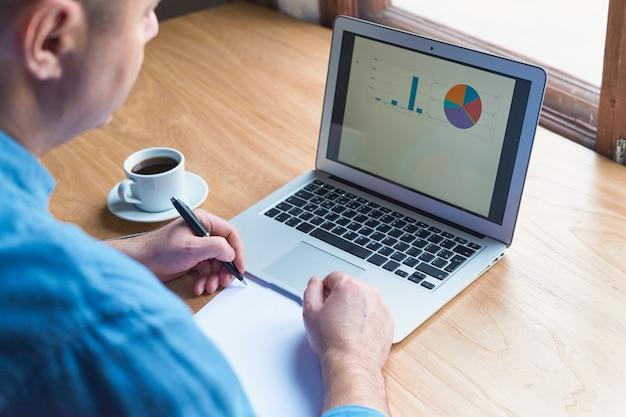 Homem irreconhecível escreve plano no papel e olha para gráficos na tela do computador, laptop. w