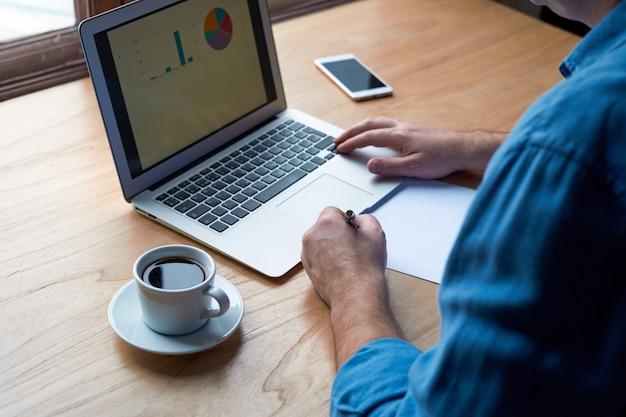 Homem irreconhecível escreve plano no papel e olha para gráficos na tela do computador, laptop.