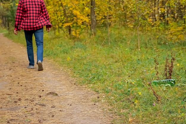 Homem irreconhecível joga uma garrafa de plástico na grama da floresta.