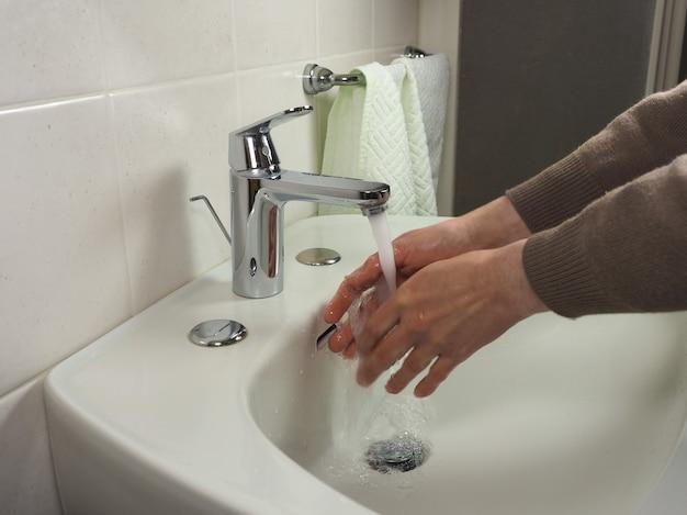 Homem irreconhecível lavando as mãos