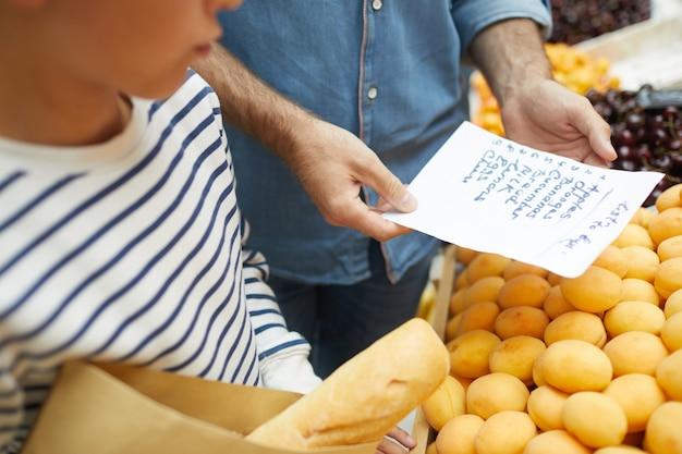 Homem irreconhecível, lendo a lista de compras
