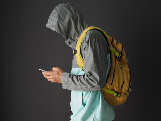 Homem irreconhecível no moletom com capuz e mochila amarela usando smartphone.