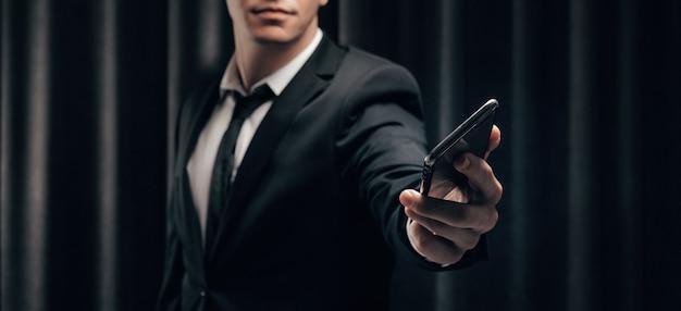Homem irreconhecível segura um telefone na frente dele