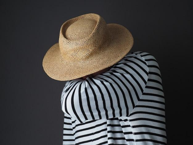 Homem irreconhecível usa chapéu preto e branco de manga comprida e palha, cobrindo a boca e o nariz com o braço enquanto espirra. homem tossindo no cotovelo.
