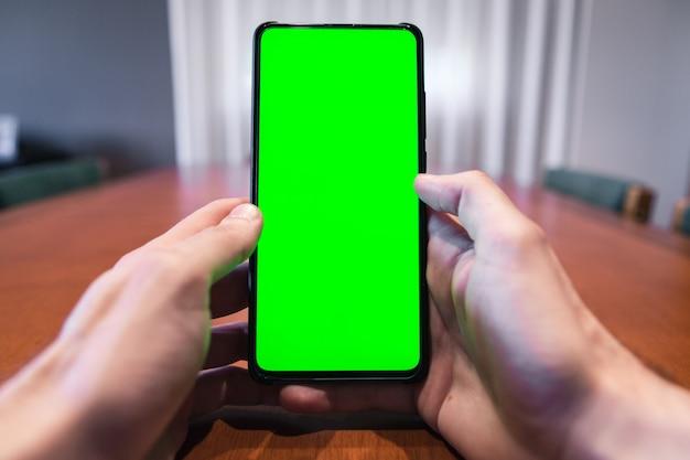 Homem irreconhecível, verificando seu telefone com tela verde em casa.