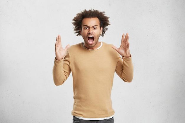 Homem irritado cheio de raiva, grita e gesticula impacientemente estando farto de tudo