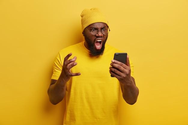 Homem irritado com barba espessa grita com raiva, tem expressão facial furiosa, recebe notícias desagradáveis, usa chapéu amarelo vivo e camiseta