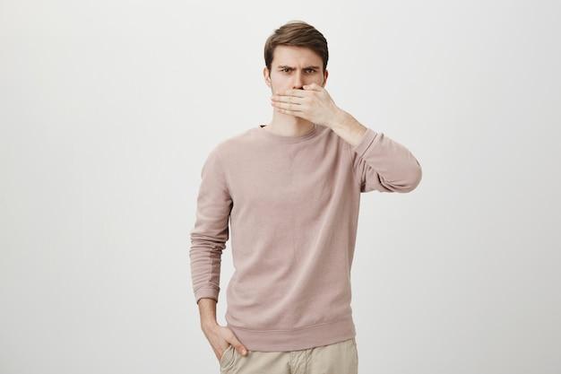 Homem irritado descontente calando a boca com a palma da mão