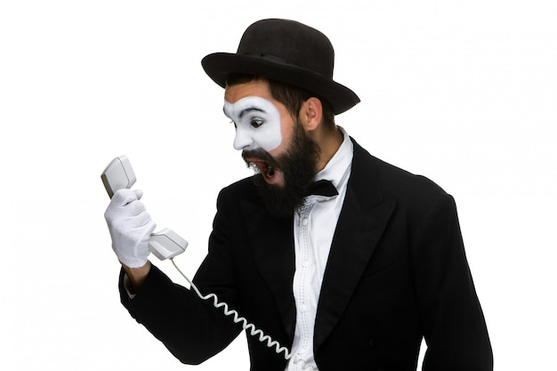 Homem irritado e irritado grita no receptor de telefone