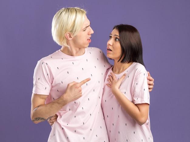 Homem irritado e mulher preocupada de pijama olhando um para o outro
