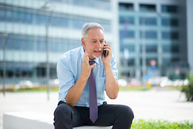 Homem irritado, falando no celular