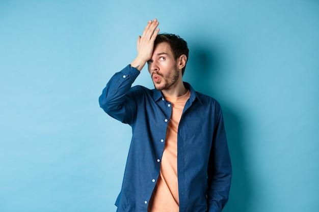 Homem irritado fazendo facepalm e revirar os olhos de algo estúpido, em pé sobre um fundo azul com a mão na testa.