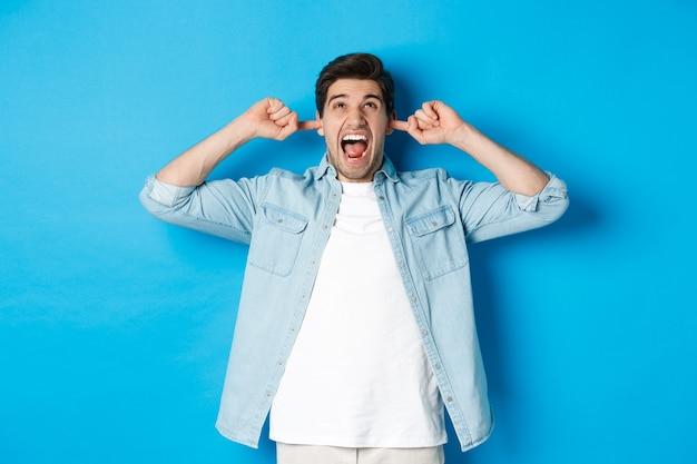 Homem irritado fecha os ouvidos dos vizinhos barulhentos, olhando para cima e gritando aborrecido, ouvindo música alta, em pé sobre a parede azul