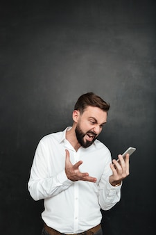 Homem irritado gritando sendo irritado enquanto procurava no smartphone na mão sobre cinza escuro