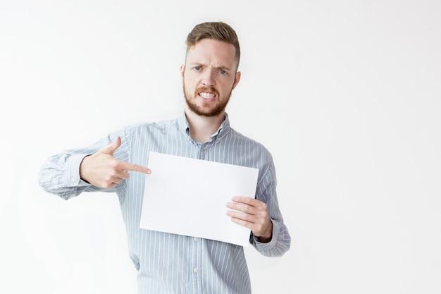 Homem irritado que aponta para a folha de papel em branco