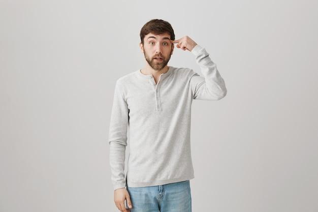 Homem irritado rolando o dedo sobre a têmpora, repreendendo comportamento estúpido