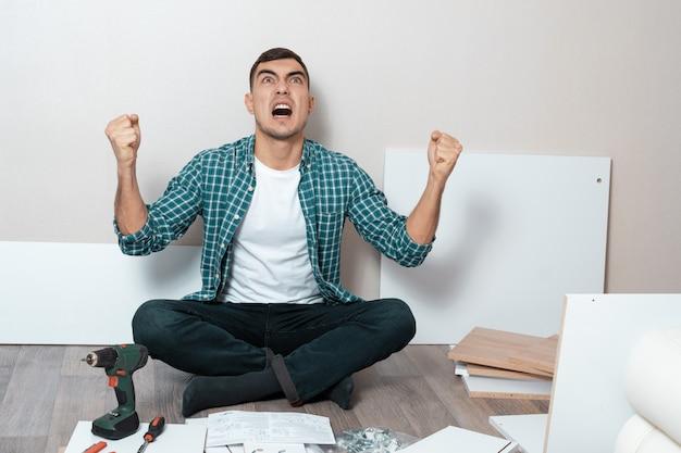 Homem irritado sentado no chão com instruções para a montagem de móveis.