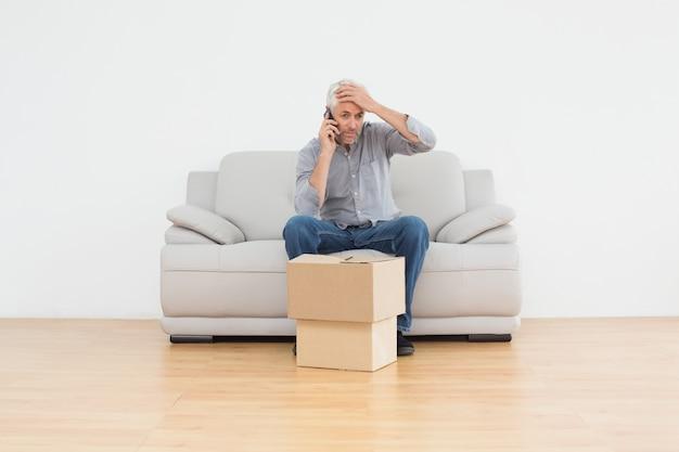 Homem irritado usando cellpone em sofá com caixas em casa