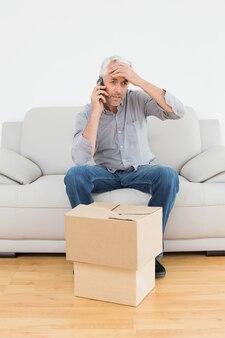 Homem irritado usando cellpone em sofá com caixas em uma nova casa