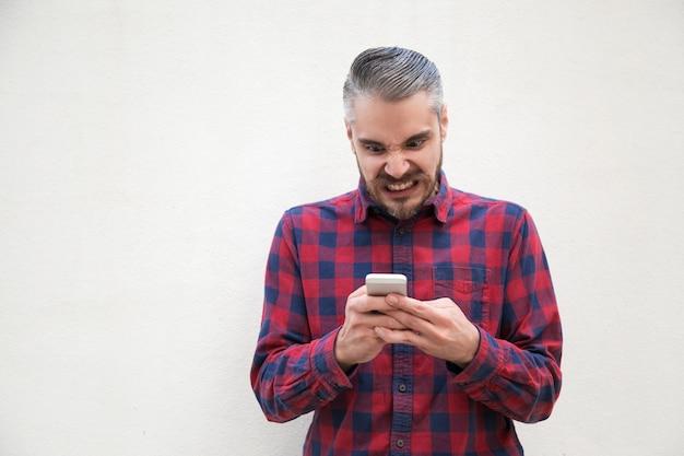 Homem irritado, usando telefone celular