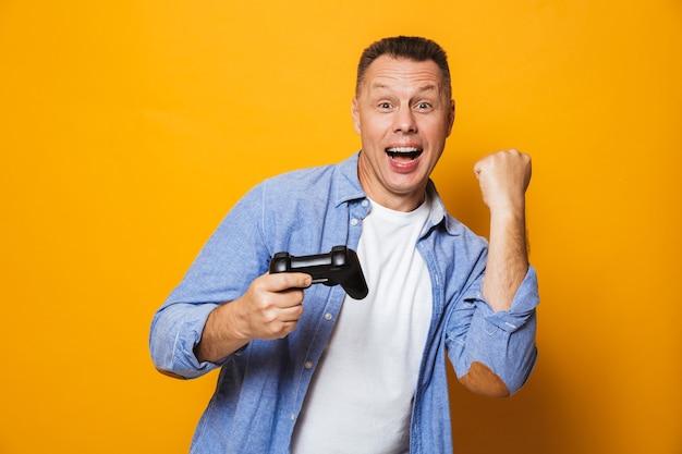 Homem isolado sobre a parede amarela jogar jogos com joystick faz gesto de vencedor.