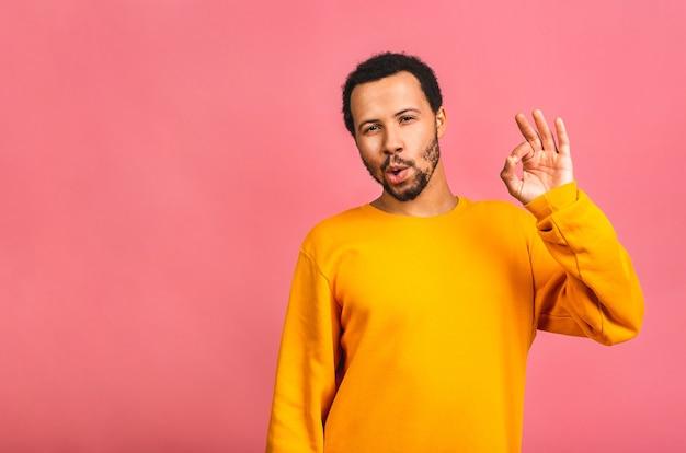 Homem isolado sobre rosa sorrindo positivo fazendo sinal de ok com a mão e os dedos. expressão de sucesso.