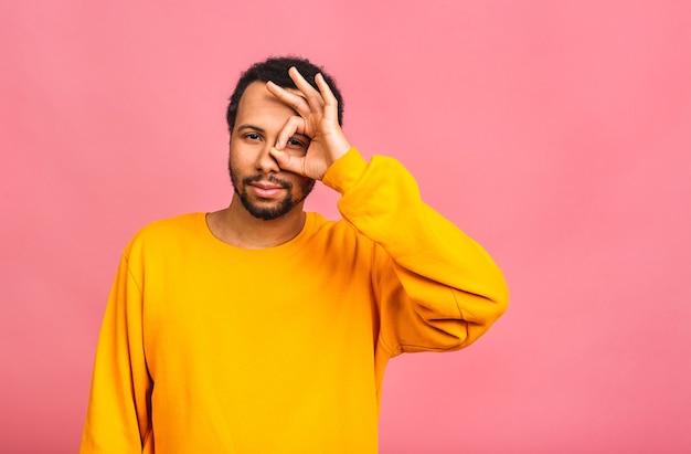 Homem isolado sobre rosa sorrindo positivo fazendo sinal de ok com a mão e os dedos