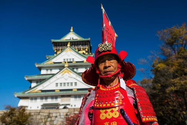 Homem japonês com samurai vermelho terno no castelo de osaka