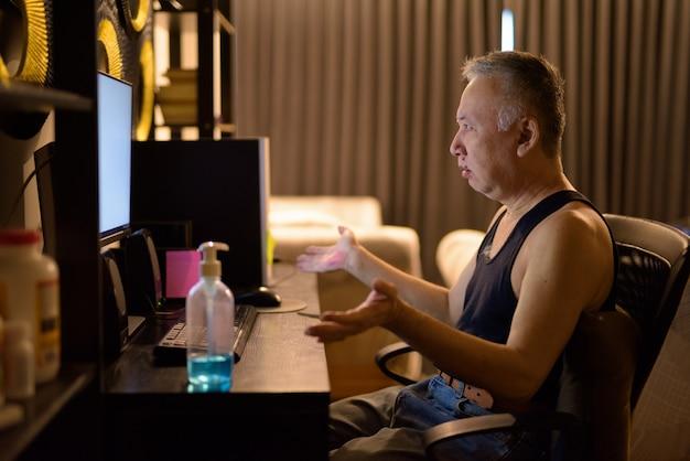 Homem japonês maduro, usando o computador e encolher os ombros os ombros em casa