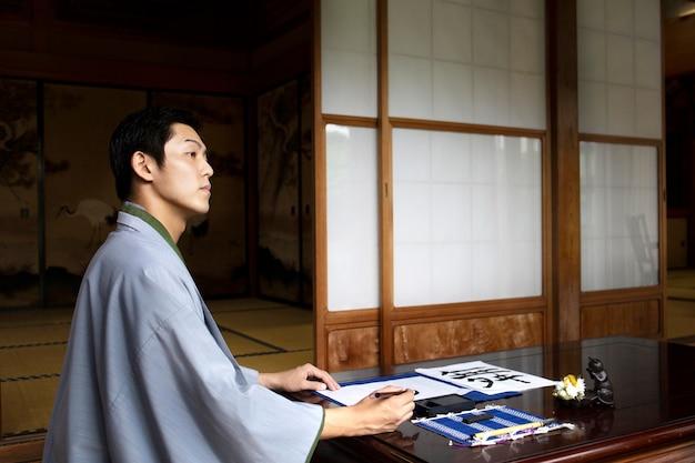 Homem japonês relaxando escrevendo à mão em um papel