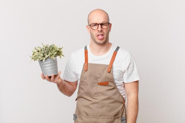 Homem jardineiro sentindo-se enojado e irritado, mostrando a língua, não gostando de algo desagradável e nojento