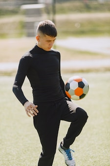 Homem joga socerl no parque. torneio de mini futebol. cara em um traje esporte preto.