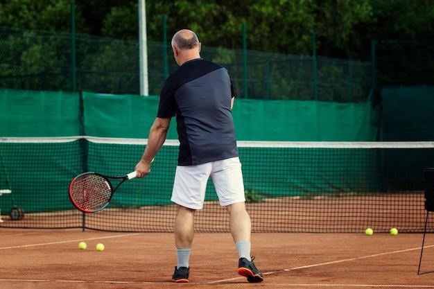 Homem joga tênis na quadra. estilo de vida ativo e saúde. vista traseira.