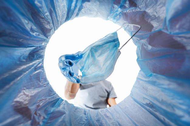 Homem joga uma máscara médica usada no lixo