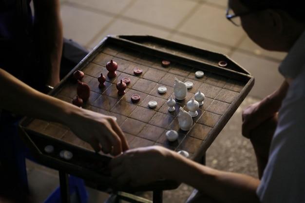 Homem joga xadrez tailandês