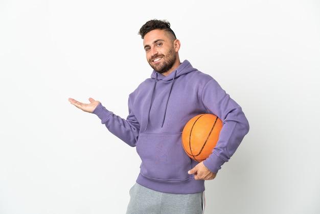 Homem jogador de basquete isolado no branco estendendo as mãos para o lado para convidar para vir