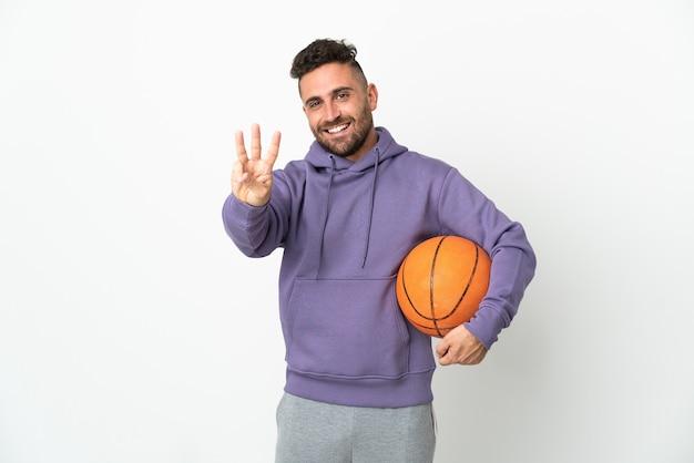 Homem jogador de basquete isolado no fundo branco feliz e contando três com os dedos