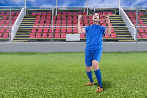 Homem jogador de futebol asiático comemora vitória no estádio