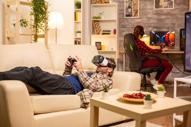 Homem-jogador usando um fone de ouvido de realidade virtual para jogar videogame na sala de estar tarde da noite