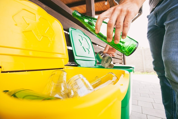 Homem jogando a garrafa de vidro e a lata em latas de lixo diferentes para separar o lixo