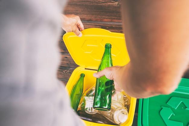 Homem jogando a garrafa de vidro em uma das três latas de lixo para classificar o lixo